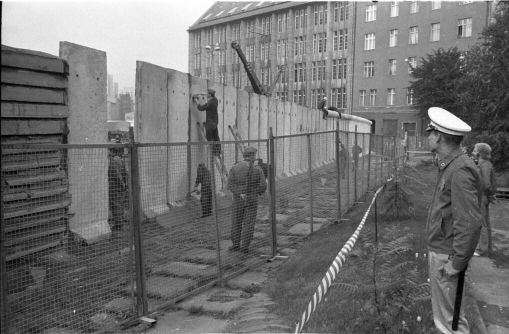 Ekipa budowlana wypełnia betonowe segmenty ściany granicznej