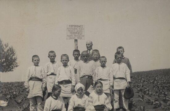 1934, Toporowce, powiat Horodenka, woj. Stanisławów. Dzieci na kursie Przysposobienia Rolniczego, na tablicy napis w języku polskim i ukraińskim