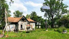 Opuszczony budynek z panelem slonecznym, ktory ma zasilac pobliskie latarnie. Przyklad przeplatania sie ruin z nowoczesna technologia